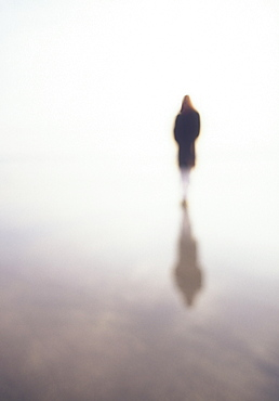 Woman reflected in wet sand on beach