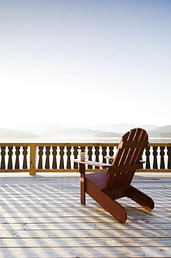 USA, New York, Lake Placid, Adirondack chair on deck by lake