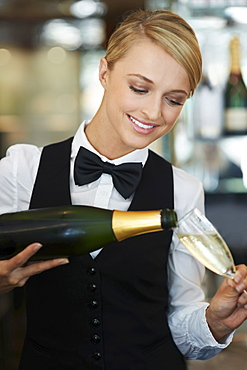 Waitress pouring champagne into champagne flute