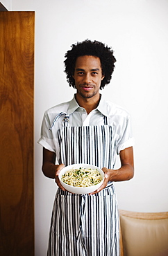 Mixed race man holding bowl of pasta