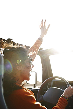 Hispanic woman raising arms while driving