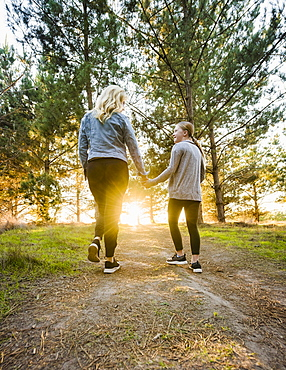 United States, California, Cambria, Rear view of mother and daughter (12-13) holding hands and walking in landscape at sunset