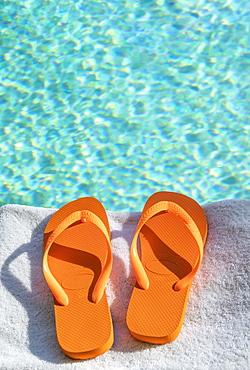 Orange flip flops on towel at poolside