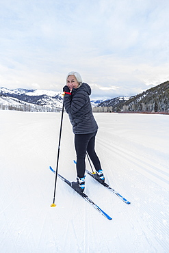 United States, Idaho, sun valley, Senior woman cross - country skiing on groomed trails