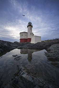United States, Oregon, Coquille River Lighthouse reflecting in water