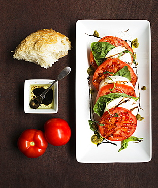 Sliced vine tomatoes and mozzarella with basil and bread
