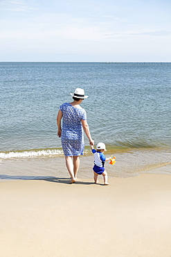 Mother and young son, holding hands, walking on beach, rear view
