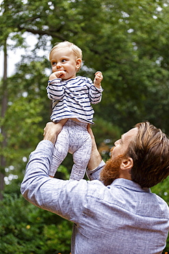 Father holding baby girl in air, outdoors