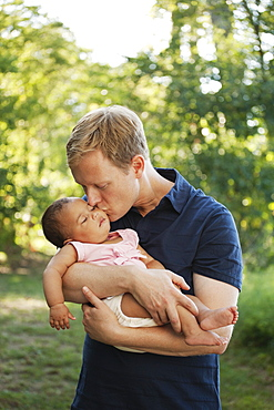 Father outdoors holding and kissing baby girl