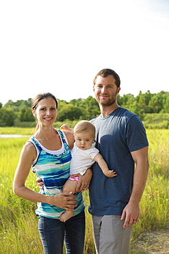 Portrait of mid adult parents carrying baby daughter by rural field