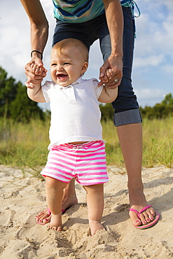 Mid adult woman holding baby daughters hands while toddling in sand