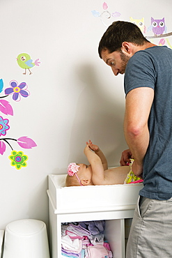 Mid adult man making faces whilst changing baby daughters nappy