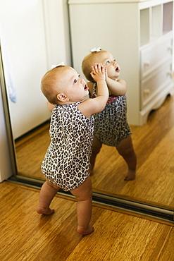 Baby girl leaning against mirrored wardrobe in bedroom