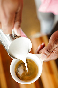 Coffee shop barista pouring milk into coffee, close up