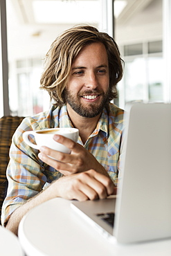Mid adult man in coffee shop, drinking coffee, using laptop