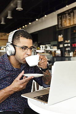 Young man in coffee shop, drinking coffee, using laptop