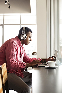 Young man in coffee shop, wearing headphones, using laptop