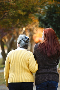 Rear view of senior woman and adult daughter strolling in autumn park