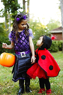Two girls with trick or treat bucket