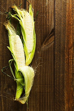 Overhead view of two corn cobs on table