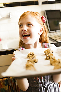 Girl holding up tray of biscuits in kitchen