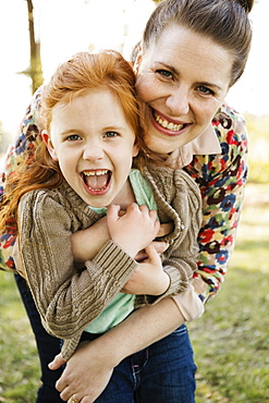 Portrait of mid adult mother hugging daughter in park