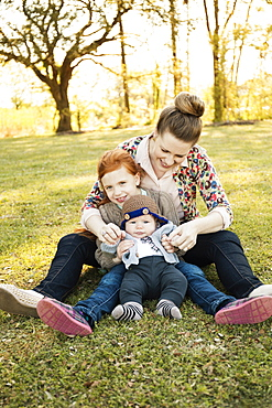 Portrait of mid adult mother, daughter and baby son in park
