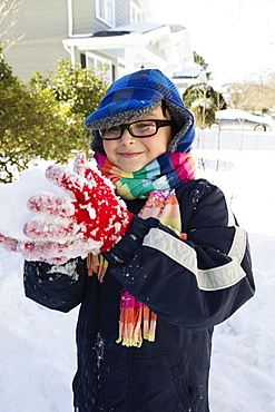 Boy making snowball, smiling