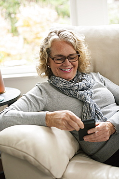 Relaxed senior woman sitting on sofa using mobile phone