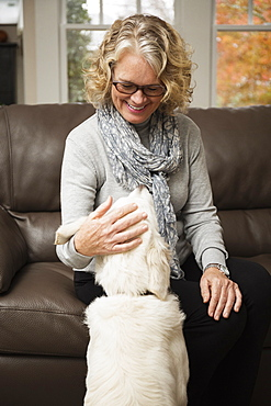 Senior woman with dog in living room