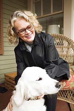 Senior woman sitting in porch with dog