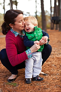 Laughing mother tickling son in park