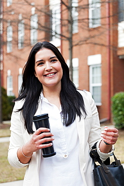 Young woman carrying travel mug