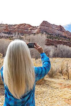 USA, Utah, Escalante, Woman taking photos in Grand Staircase-Escalante National Monument