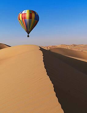 Dubai, United Arab Emirates, Colorful hot air balloon flying over sand dunes