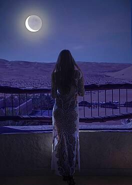Dubai, United Arab Emirates, Woman in luxury resort in desert watching moon and starry sky at night