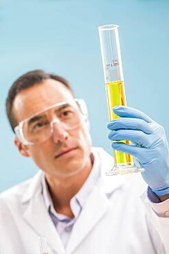 Scientist looking at yellow liquid in measuring beaker