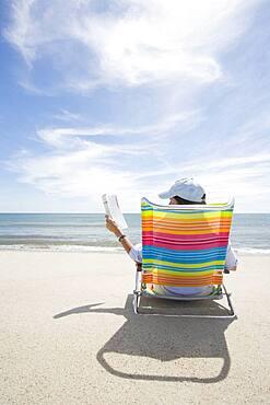 USA, Massachusetts, Cape Cod, Nantucket Island, Rear view of woman on colorful beach chair reading magazine on beach
