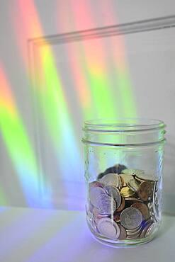 Jar of coins with rainbow light