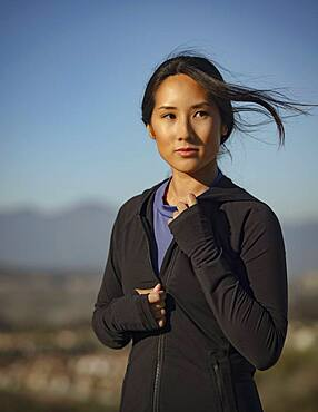 Portrait of pensive woman in sports clothing standing in landscape