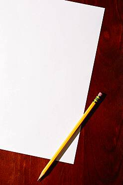Overhead view of blank paper and pencil on desktop