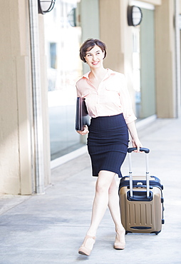 Portrait of business woman pulling suitcase, USA, New Jersey, Jersey City