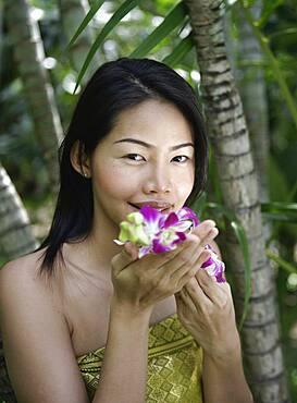 Thailand, Koh Samui Island, Portrait of smiling woman smelling orchids