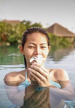 Thailand, Koh Samui Island, Portrait of smiling woman holding frangipani flower in water