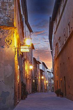 Italy, Tuscany, Val D'Orcia, Pienza, Narrow alley and illuminated buildings in old town at dusk