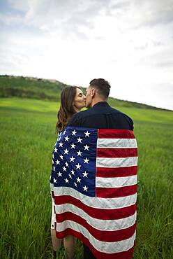 Young couple wrapped in American flag kissing in wheat field