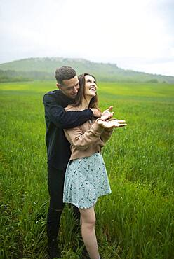 Young couple embracing in wheat field in rain
