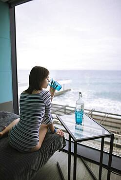 Rear view of woman drinking water in hotel with view on sea