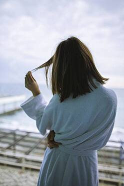 Rear view of woman in bathrobe in hotel with view on sea