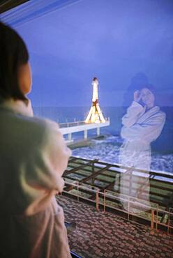 Rear view of woman in bathrobe in hotel with view on sea at night